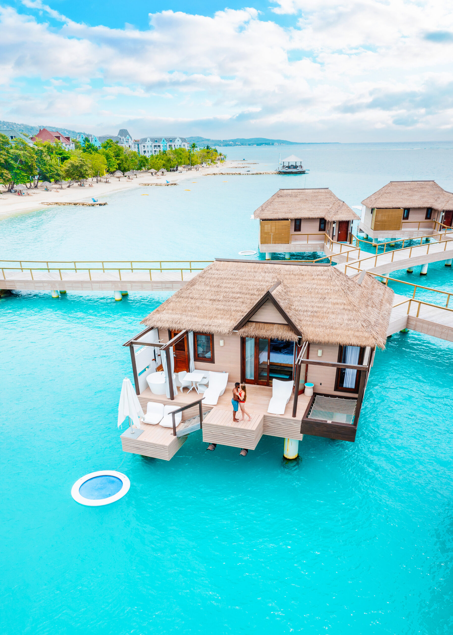 A couple standing on the deck of an overwater bungalows in Jamaica where there are sun loungers, a tub, a bistro set, an outdoor hammock, and a floating ring