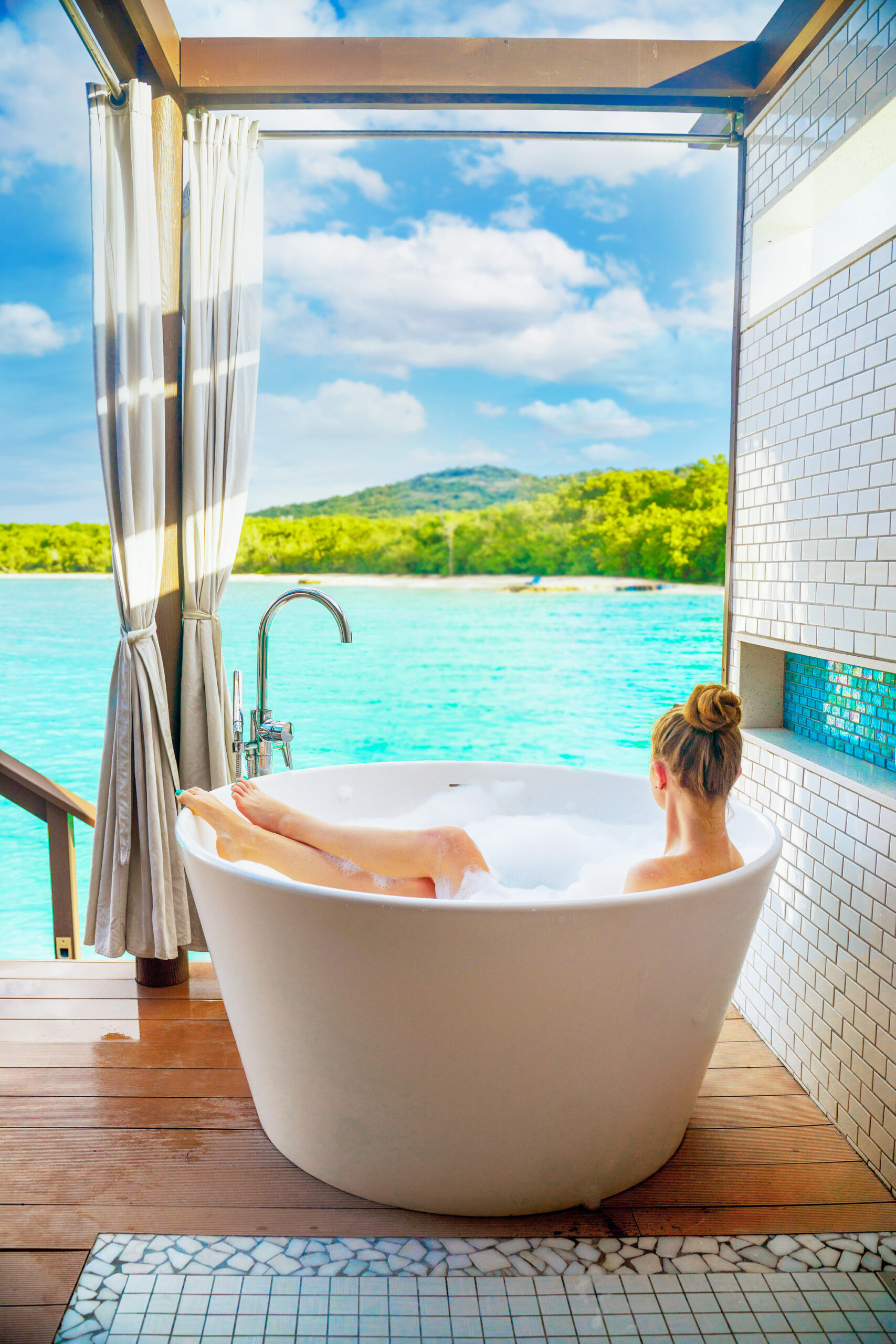 A woman sitting in an outdoor tub looking out at a view of the beach and mountains