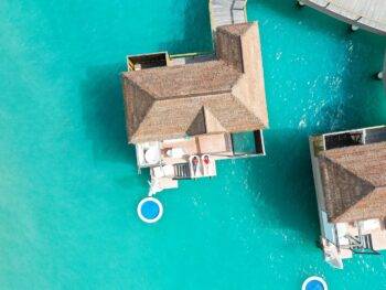 drone photo of couple sitting on overwater bungalows in jamaica at sandals south coast
