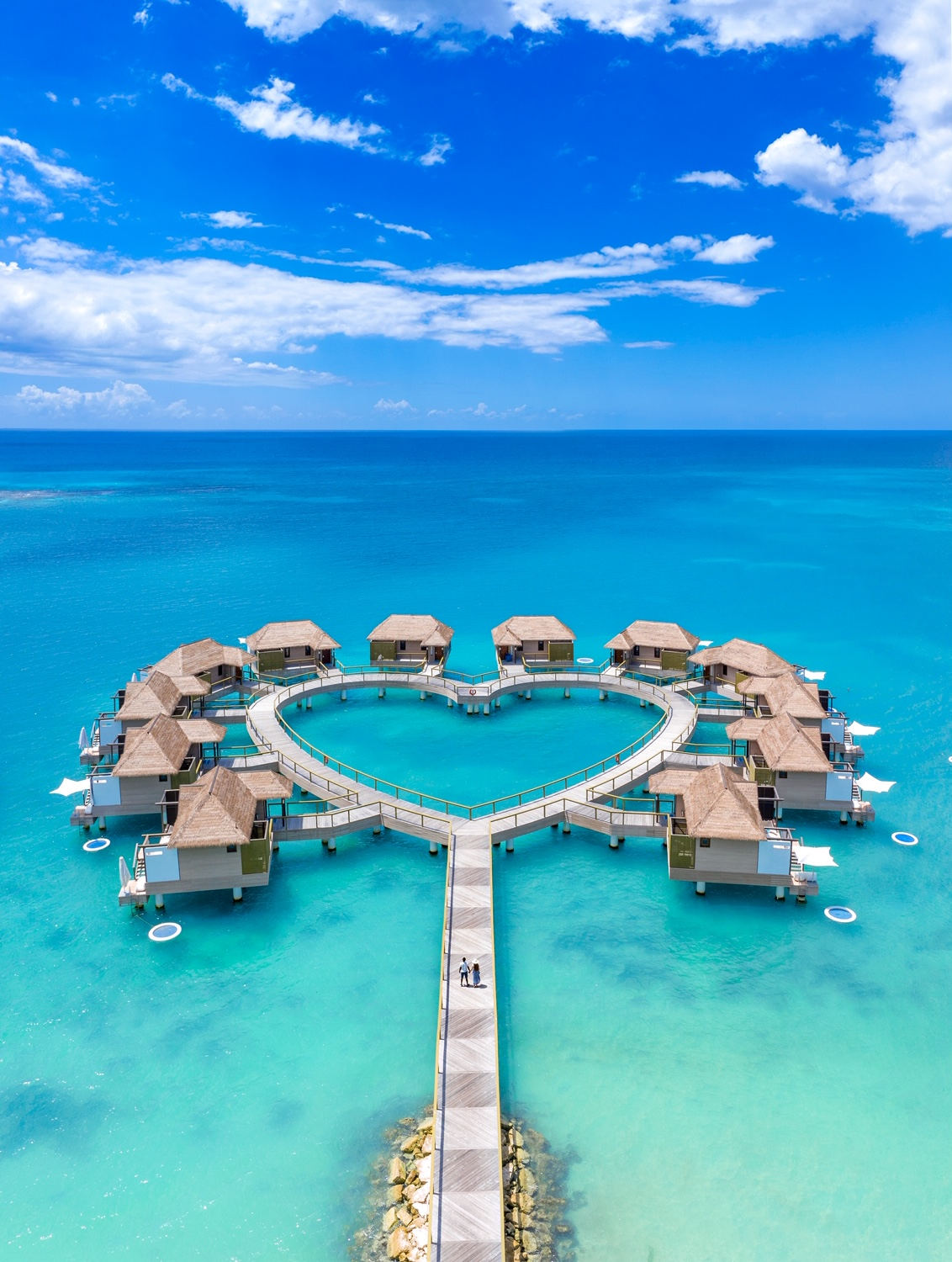 an aerial photo of two people standing on the dock facing a heart shaped collection of overwater bungalows in Jamaica