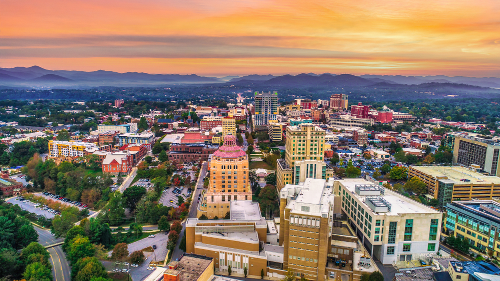 An aerial photo of Asheville North Carolina at sunset with a yellow sky and mountains in the distance