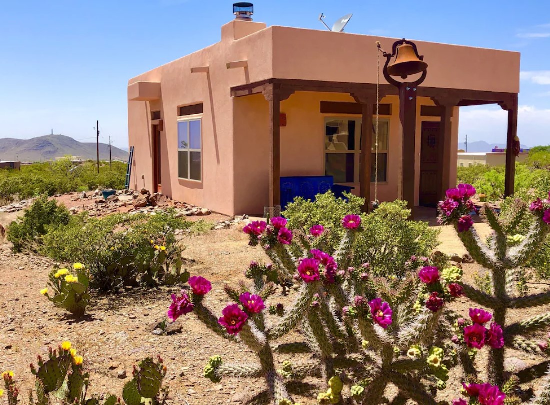 A house made out of red clay with dark wood accents and a covered front porch. There is a standing bell in front of the house, as well as yellow and pink desert flowers
