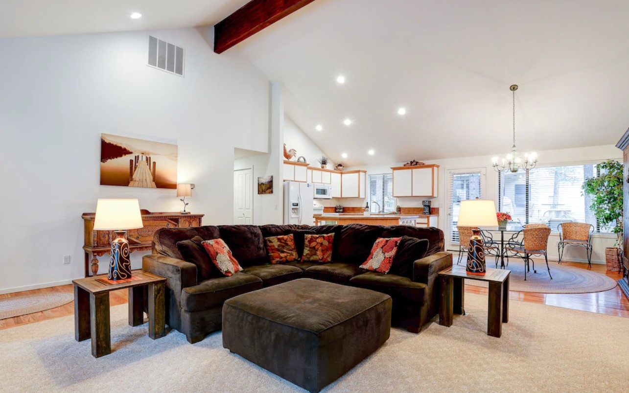 The large living area of one of the best vacation rentals in Oregon with a large brown sectional sofa, vaulted ceilings, a fully equipped kitchen, and a small dining area.