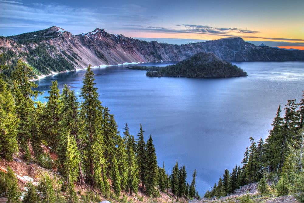 View of the caldera of Crater Lake at sunrise. Wizard Island is visible and the sunset is bringing out the purple tones of the sloping shores of the lake.