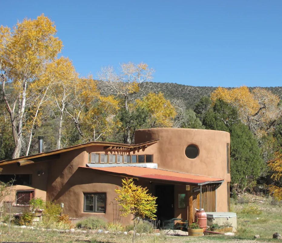 A uniquely shaped adobe clay home in a mountain valley with a mountain in the distance and trees with green and yellow foliage on them.