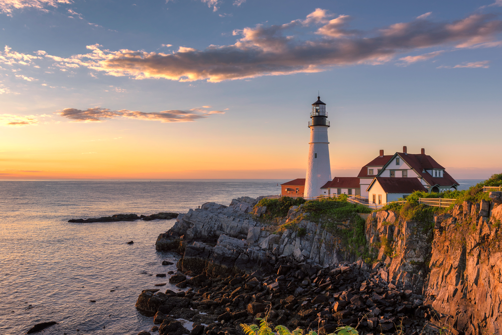 A lighthouse on the coast of maine's rocky shore at sunset. It is a large white lighthouse with large white buildings near it.