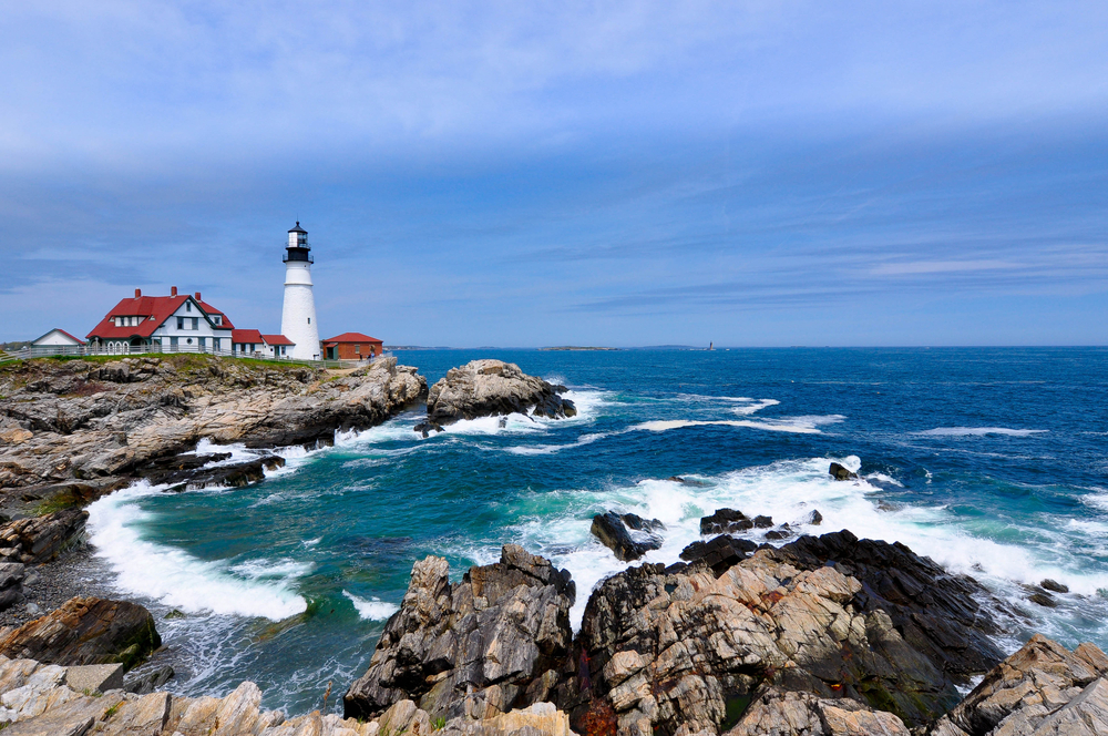 A lighthouse on a rocky coast in Maine on a sunny day
