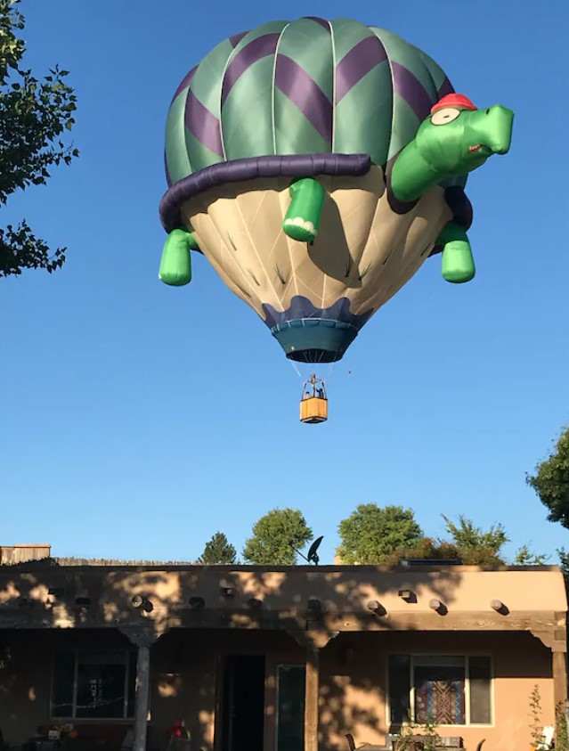A hot air balloon that looks like a turtle wearing a red hat and glass flying over a clay adobe home. The hot air balloon has arms, a green shell with purple stripes, and a tan 'underbelly'. It is floating very close to the adobe style home