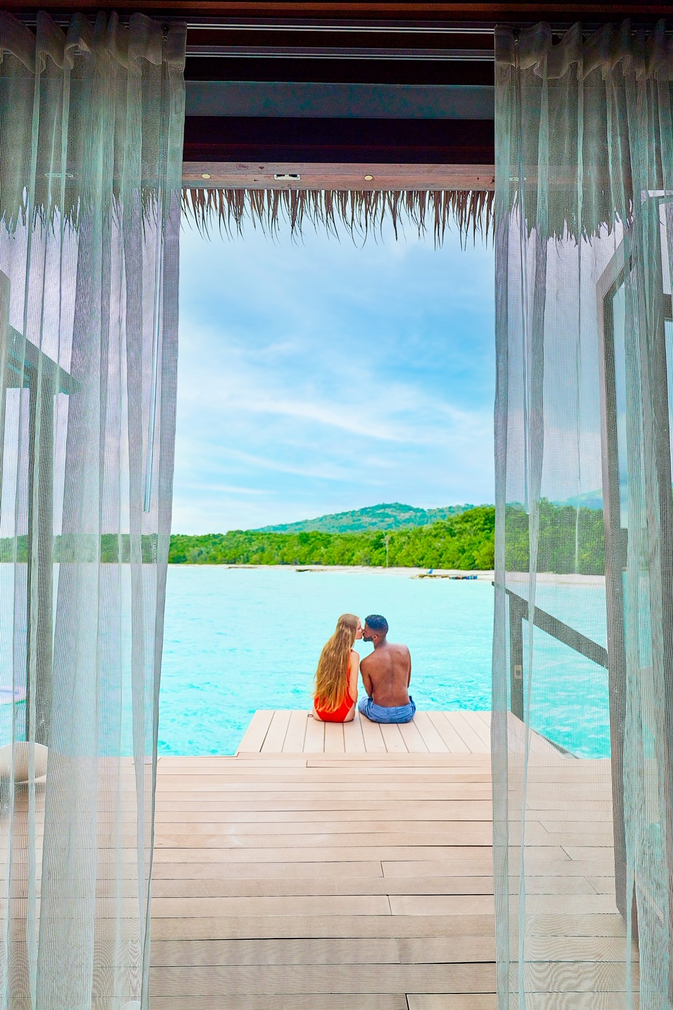 A couple sitting and kissing on the deck of an overwater bungalow with a view of the ocean and mountains