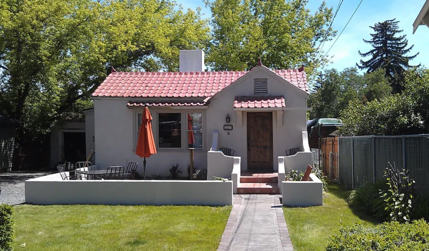 A cute historic bungalow with white stucco, a front courtyard, and a red shingled roof with a small yard in the front one of the best vacation rentals in Oregon