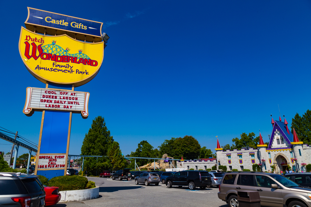 The main entrance to Dutch Wonderland, a amusement park in Amish country Pennsylvania. The sign is yellow and kind of shaped like a crown. At the entrance of the park is a large castle.