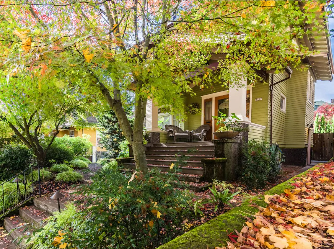 The exterior of a pea green Craftsman-style home with a large front porch and stone steps. There are large trees and shrubs in front of the house. It is one of the best vacation rentals in Oregon.