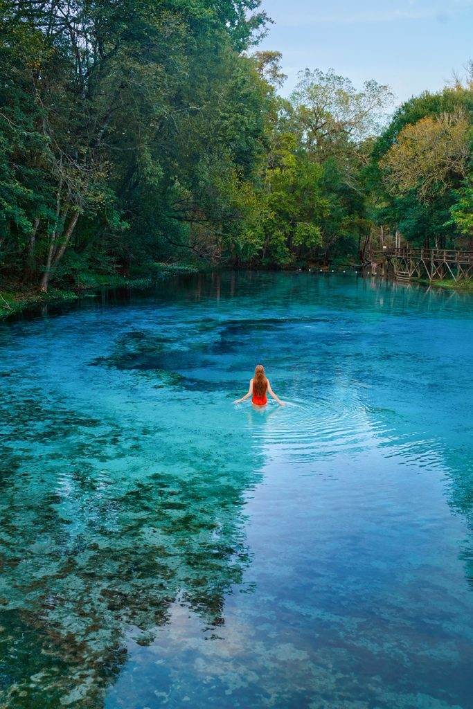 A woman in a red bathing suit with long hair standing in a crystal blue Florida spring. One of the best east coast road trip destinations.