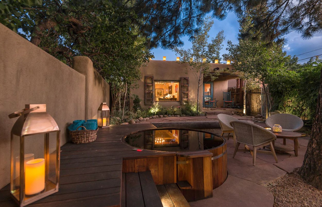 The backyard of a historic adobe in Santa Fe New Mexico. It has a large stone patio with seating, a cedar plank hot tub, and lots of lights. The home is in the back with a big window and a small deck with two rocking chairs. Airbnbs in New Mexico
