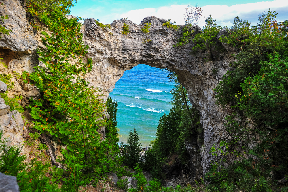 A natural stone arch on Mackinac Island Michigan with water in the background and surrounded by greenery
