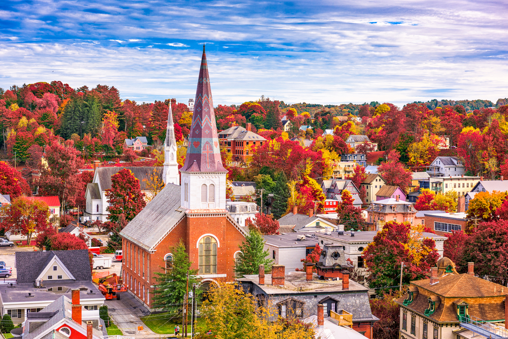 An aerial view of a small town in Vermont. You can see a large church steeple with decorations on it. The town is super cute and surrounded by red, yellow, and orange fall leaves
