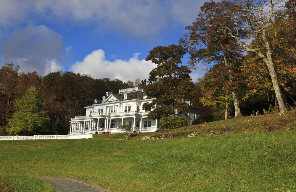 The Moses H. Cone Manor on the Blue Ridge Parkway surrounded by a grassy lawn and large old trees. The sky is very blue with big fluffy clouds. Its a great stop on any east coast road trip.