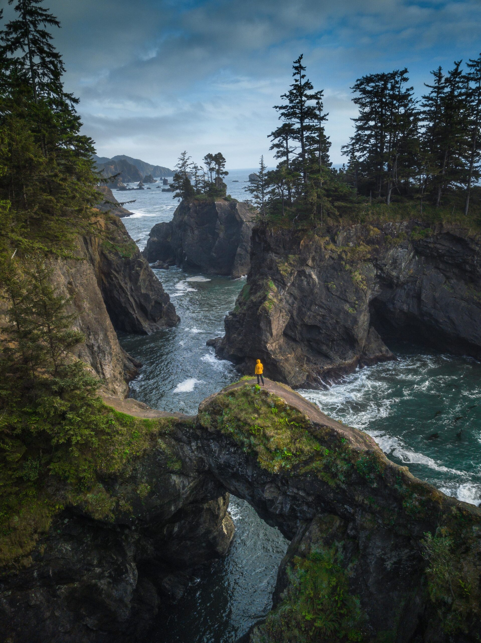 A person in a yellow coat standing on a narrow path surrounded by rocky cliffs and water on the Oregon Coast