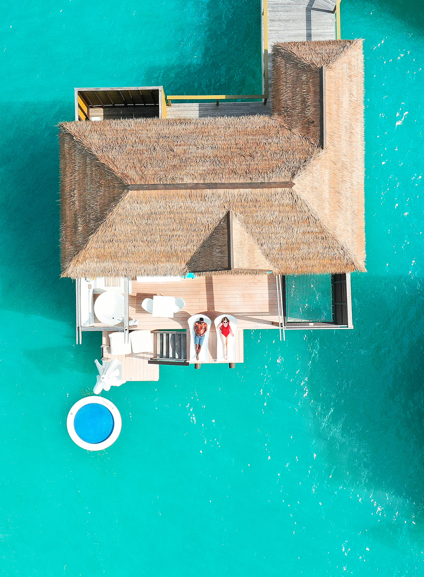 couple relaxing on deck of an overwater bungalows in jamaica in a red swimsuit with blue water