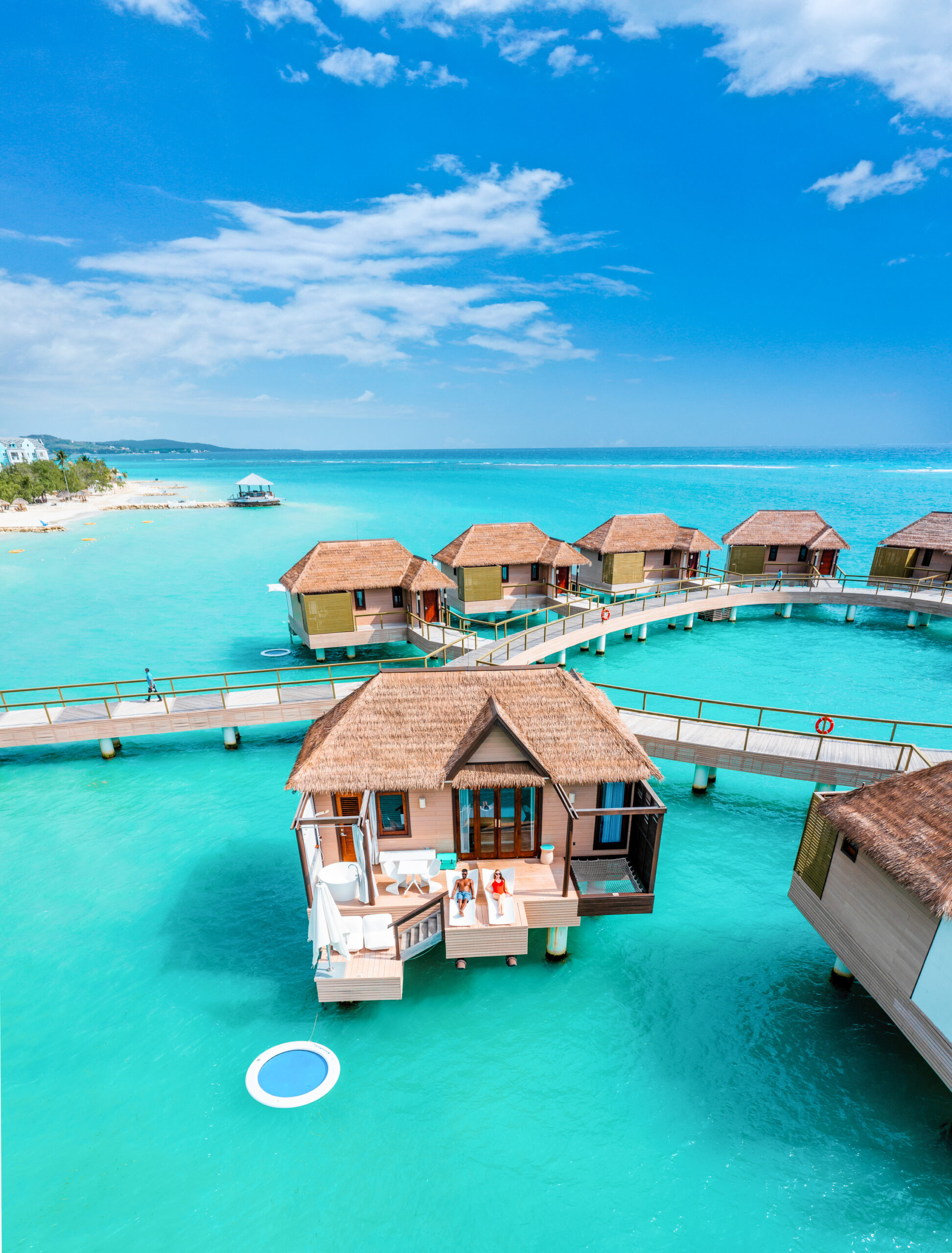 drone photo of couple sitting on an overwater bungalow in jamaica at Sandals South Coast in the caribbean