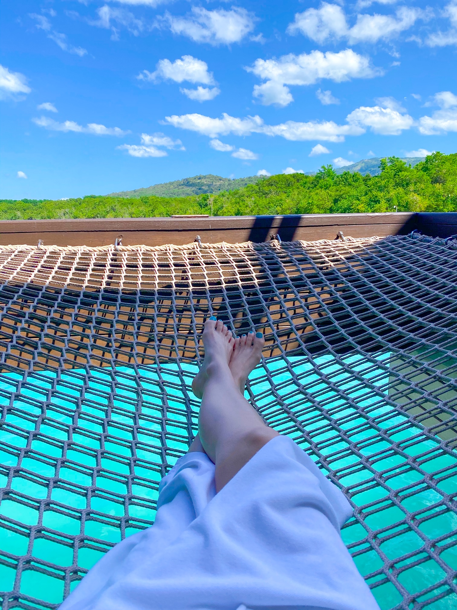 sitting in a netting over the ocean at an overwater bungalows in jamaica