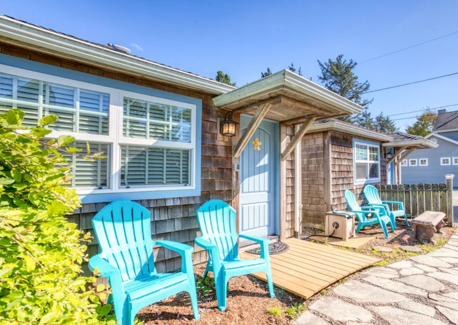 The exterior of a raw wood shingled cottage with a pale blue door, pale blue trim, and bright blue Adirondack chairs in front of it with a bush in the corner on a sunny day.