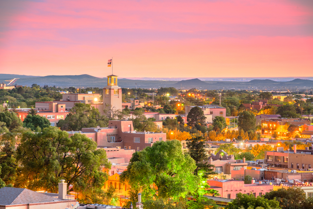A view of Santa Fe New Mexico at sunset with a pink sky, the plaster buildings tinted pink from the sky, and the buildings lit up