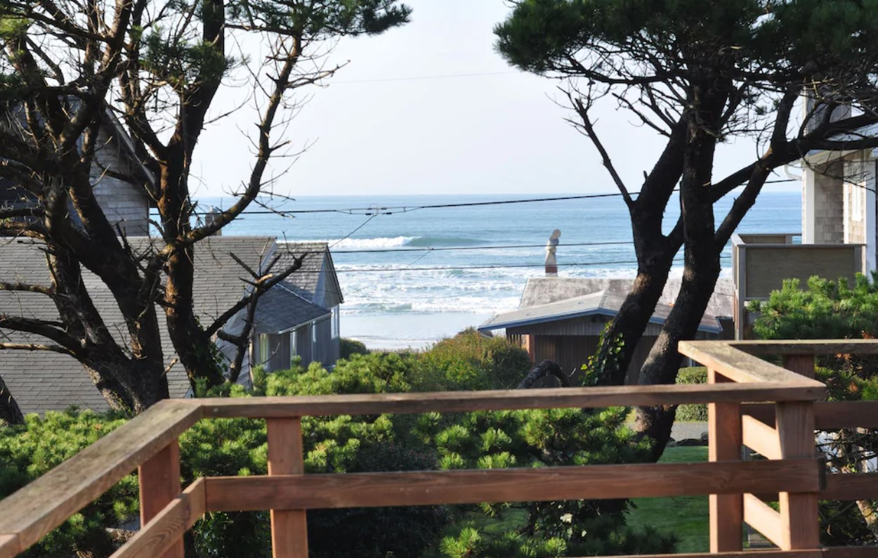 The view of the ocean from the deck of an Oregon vacation rental with houses in the distance, and trees and shrubs near the deck