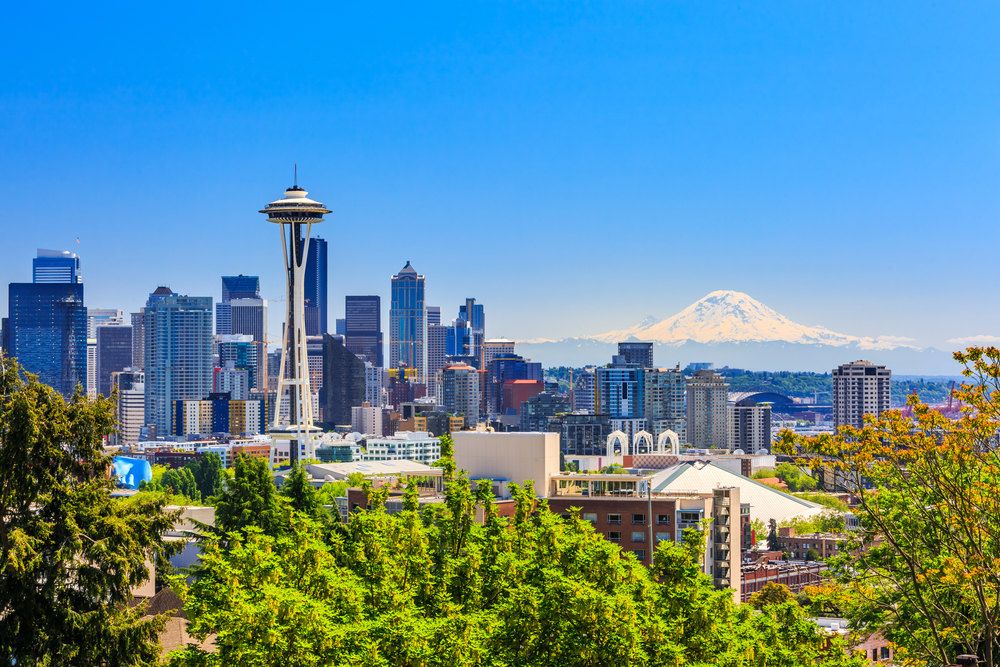 The Seattle skyline with the space needle in the front and a mountain in the background on a sunny day one of the best weekend getaways in the usa