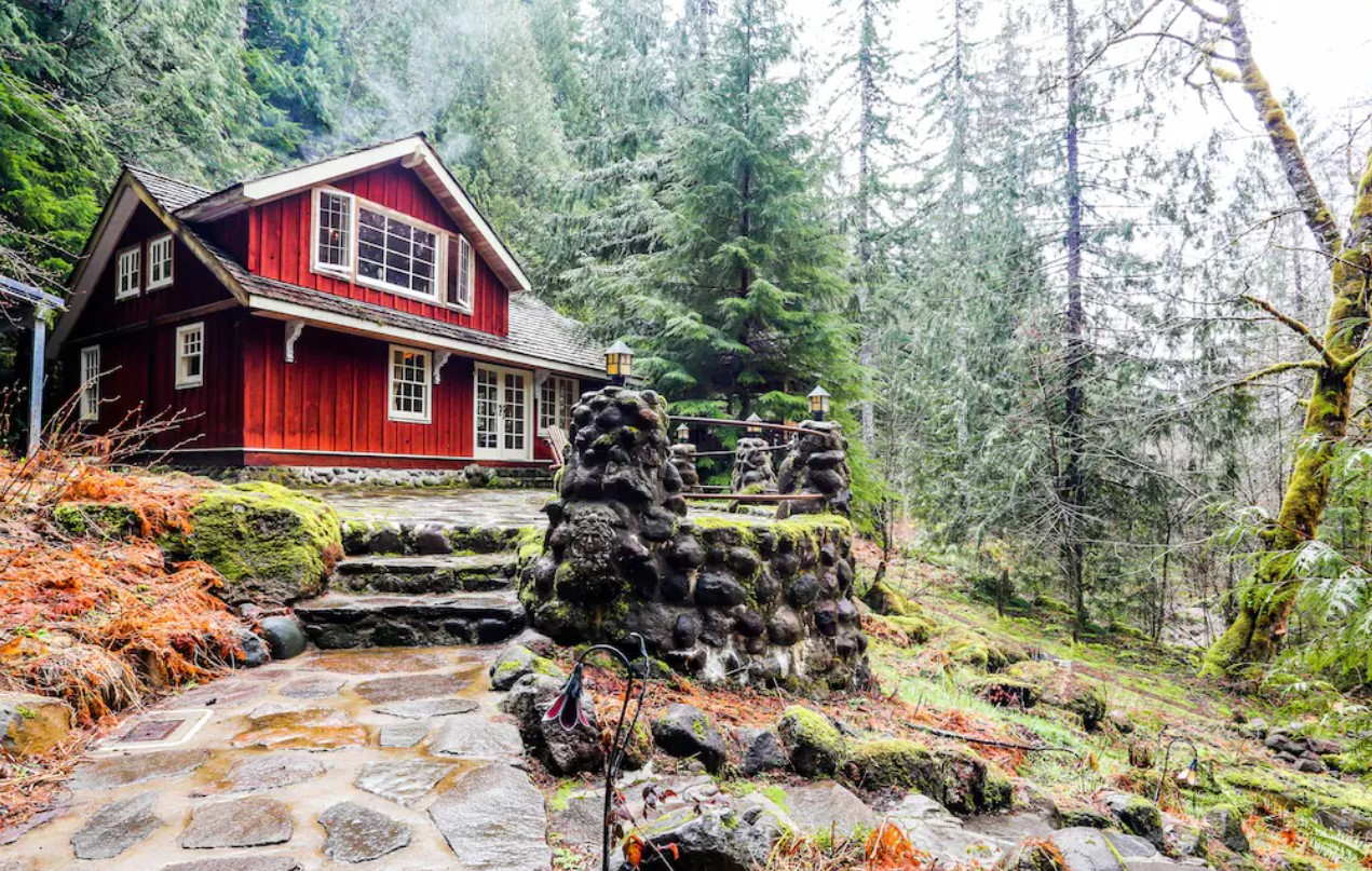 The exterior of a bright red painted lodge in the woods surrounded by trees with stone steps leading to a stone patio in front of the lodge house one of the best vacation rentals in Oregon
