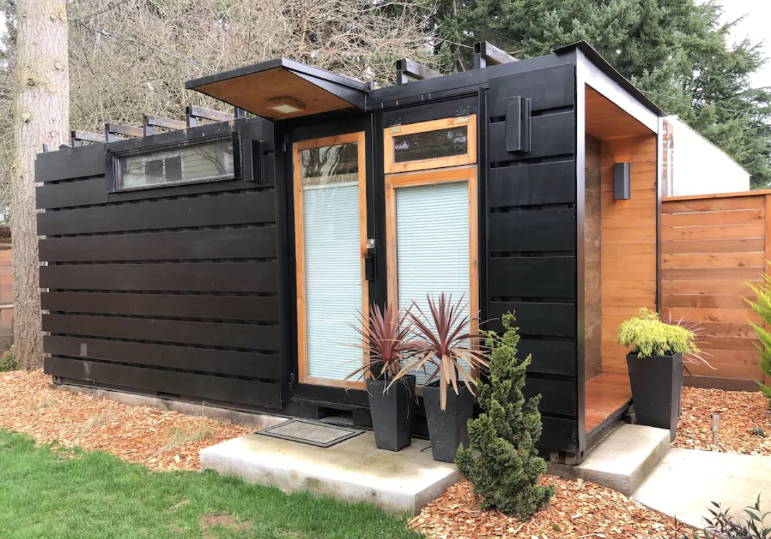 The exterior of a modern style black shipping container with natural wood accents. There is pebble, potted plants, and a small patch of grass in front of the shipping container. It is one of the best vacation rentals in Oregon