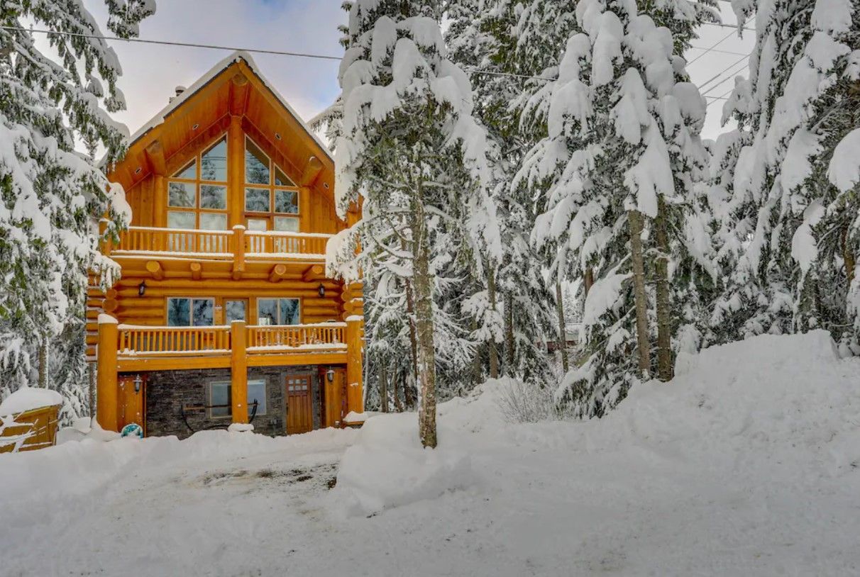 The exterior of a two story wood lodge with two decks and plenty of windows, surrounded by snow and trees covered in snow