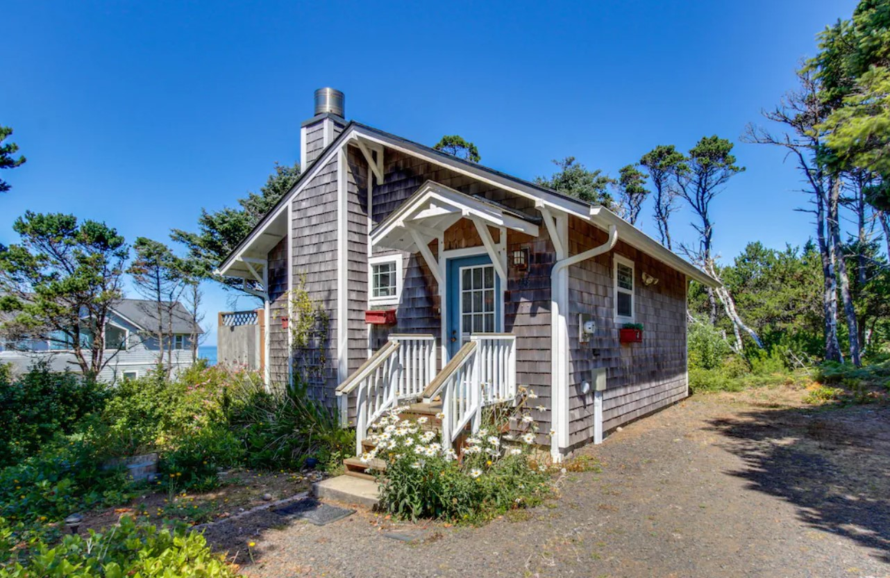 The exterior of a charming beach cottage that has grey shingles, a bright blue door, white trim, and a chimney. In front of the house, there is a small garden with white flowers and shrubs. It is one of the best vacation rentals in Oregon.
