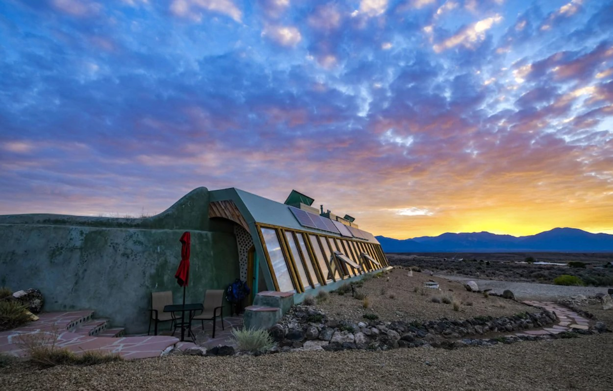 The exterior of an earthship in the New Mexico desert. It is painted a sage green, and has windows all along one side of it. There is also a small patio with a table and chairs and desert mountains in the distance. It is sunset.