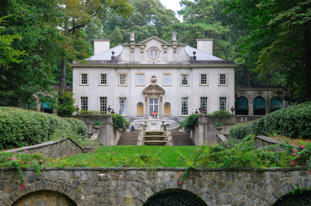 An old manor named the Swan House in the middle of Atlanta. It is a colonial greek revival style home that is cream with lots of windows. There is a lawn and manicured garden in front of it. It is surrounded by trees.