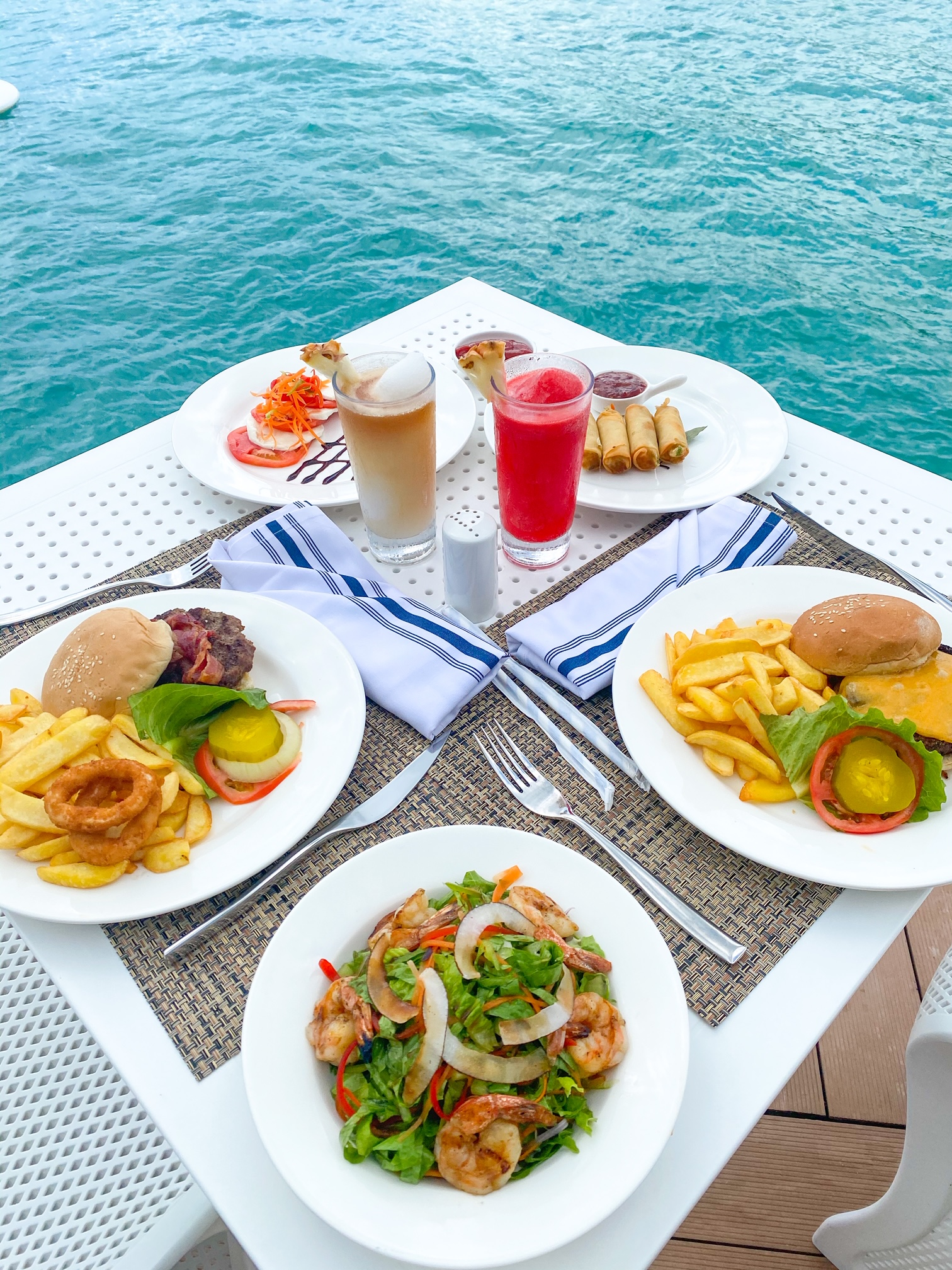 Several plates of food and a few drinks on a white table with the ocean in the background
