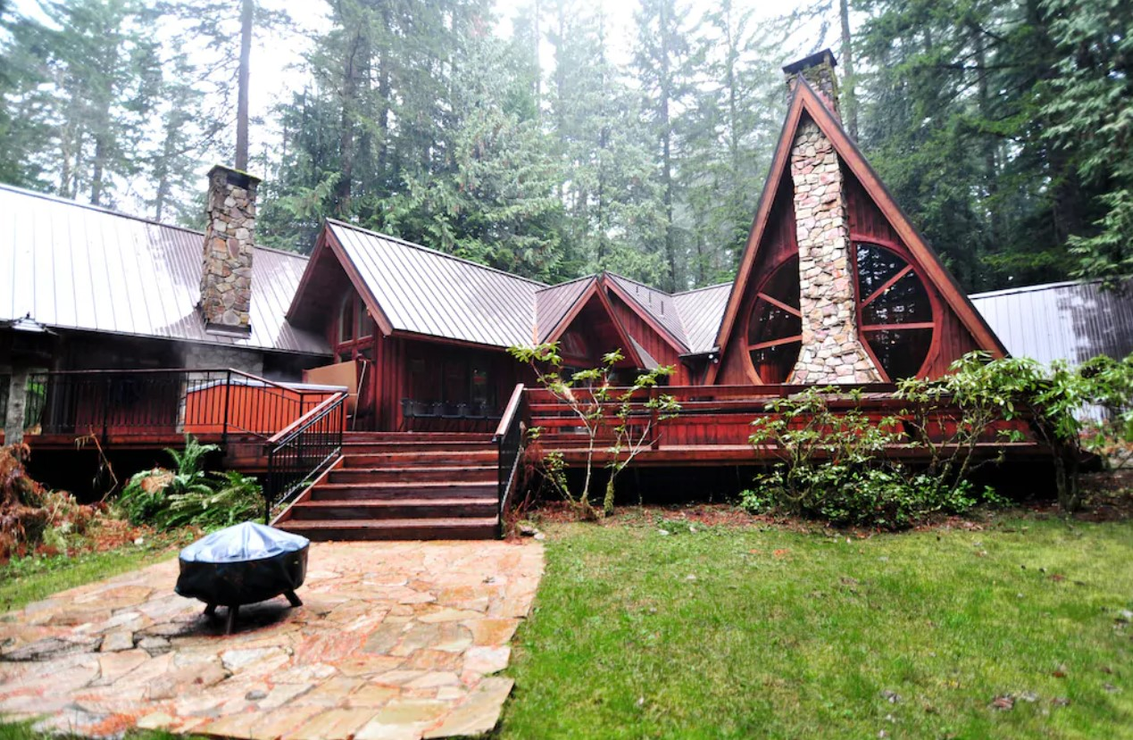 A large dark red lodge in the woods with several peaks, and two large semi-circle windows around a stone chimney. There is also a large deck, an outdoor fire pit, and plenty of trees
