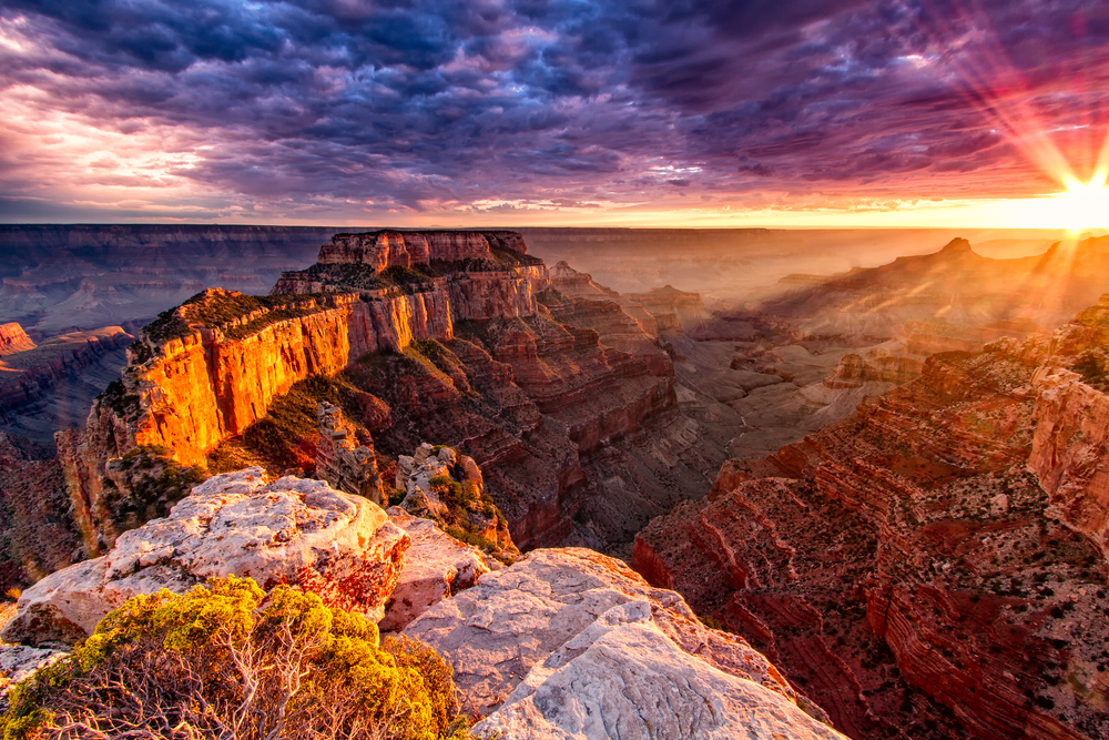 The Grand Canyon at sunset on a cloudy day with pink and purple sky one of the best weekend getaways in the USA