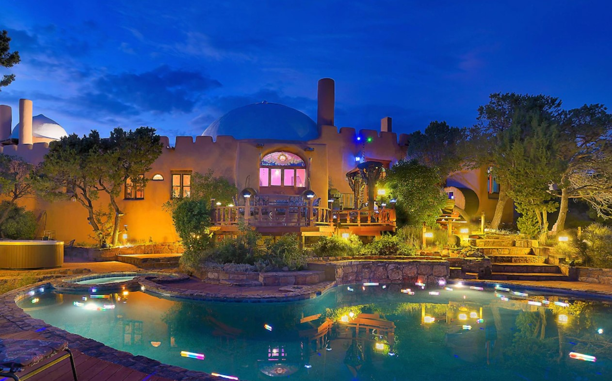 A large home with a domed ceiling, stained glass windows, a massive pool with lights in it, a green space with stone steps and trees, and more at twilight.