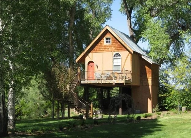 A cute fairy tale cottage style treehouse with cedar shingling, a curved orange door, and steps that lead up to the treehouse and deck. It is surrounded by grass and tall trees