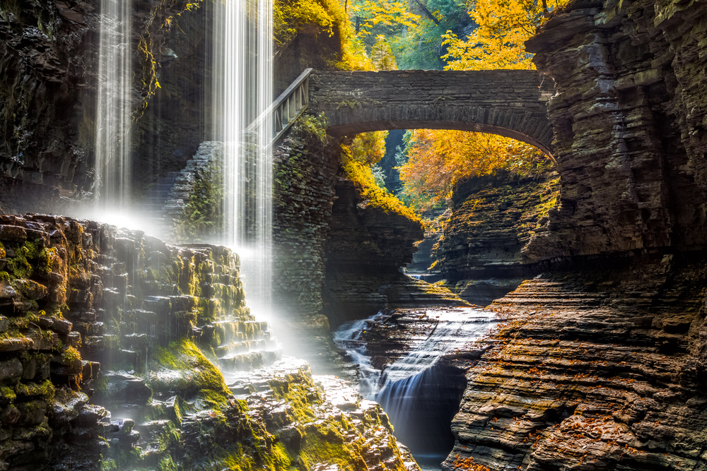 A waterfall falling down into a ravine with a stone bridge and staircase. There are trees with yellow leaves behind the rock formations and moss growing on the rocks