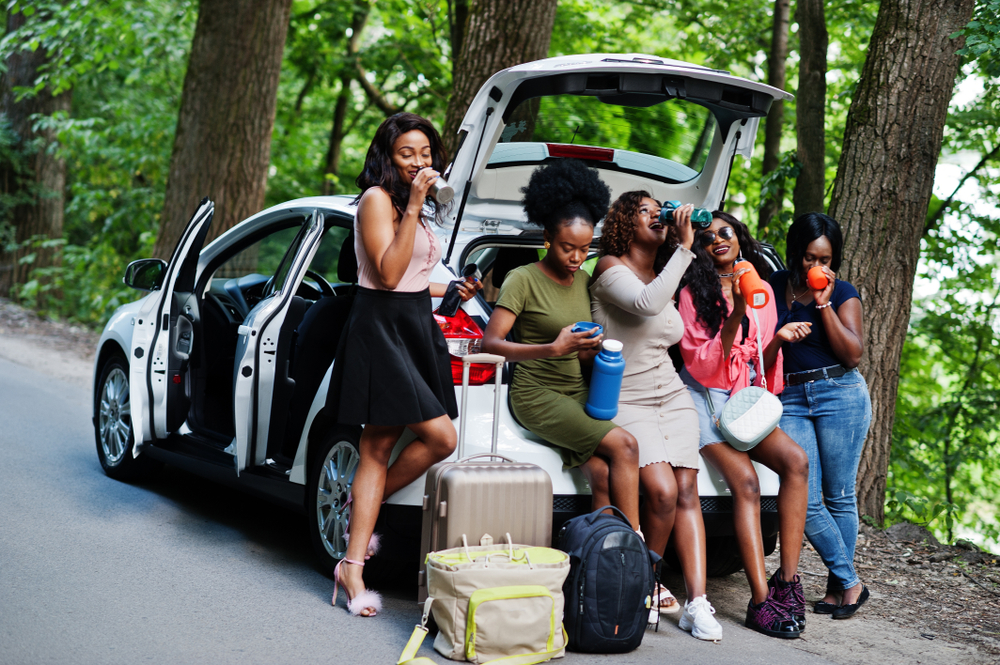 A group of Black women sitting on the back of a car drinking out of water bottles on a road trip