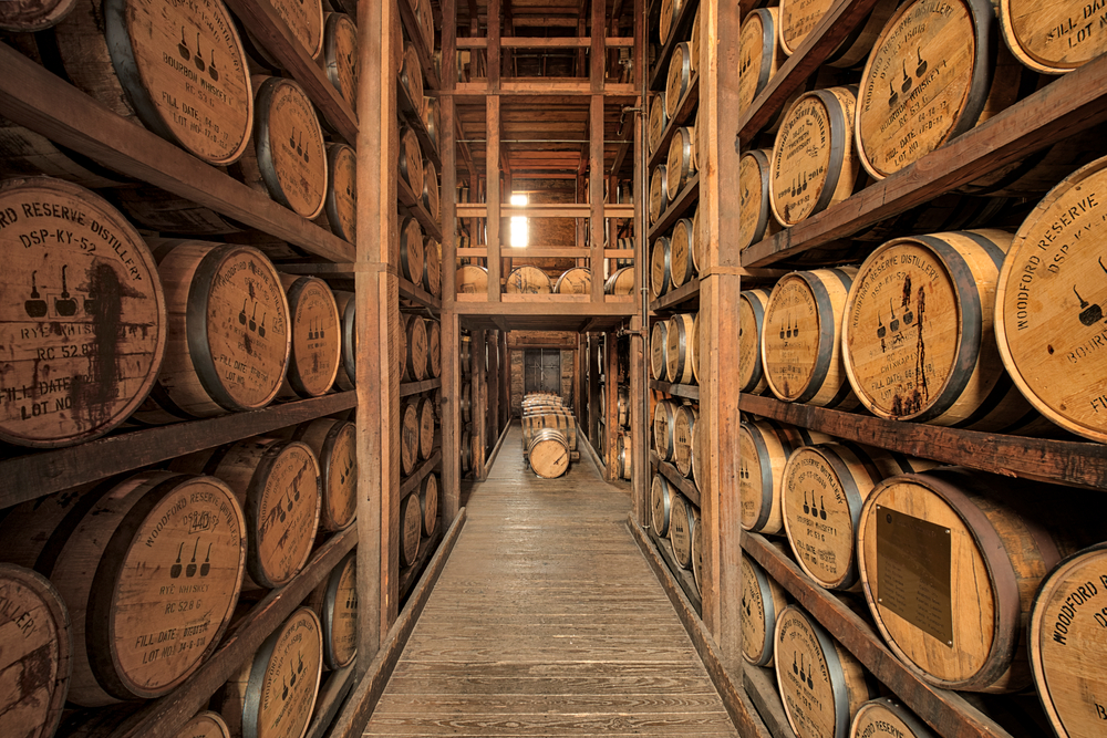 A room full of shelves with barrels of bourbon stacked on top of each other. One of the best east coast road trip stops
