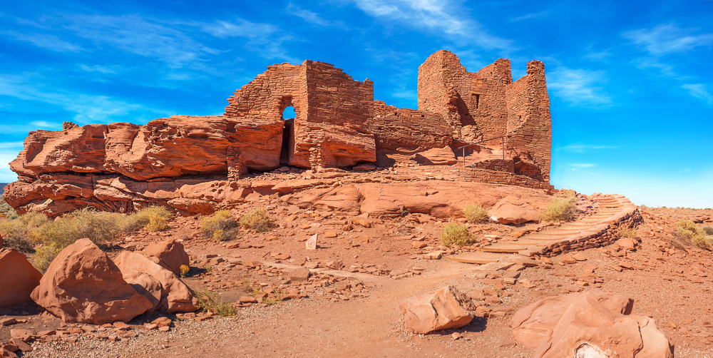 A historic pueblos at the Wupatki National Monument. They are ruins of what once was a house made of red sandstone bricks. It is a bright sunny day.