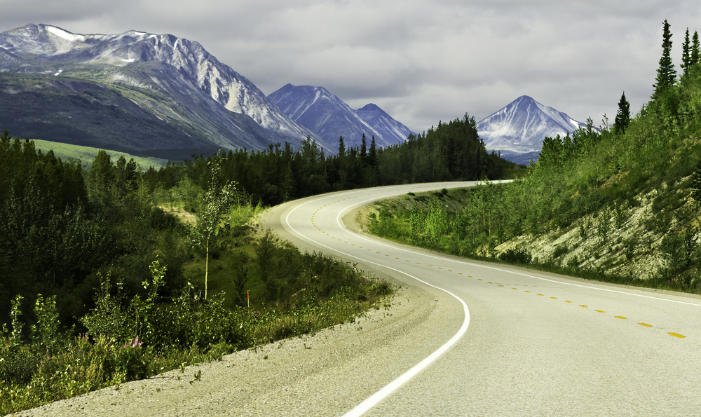 A winding road in Alaska with tall snow topped mountains in the distance. The road is surrounded by greenery and large trees. It is cloudy.