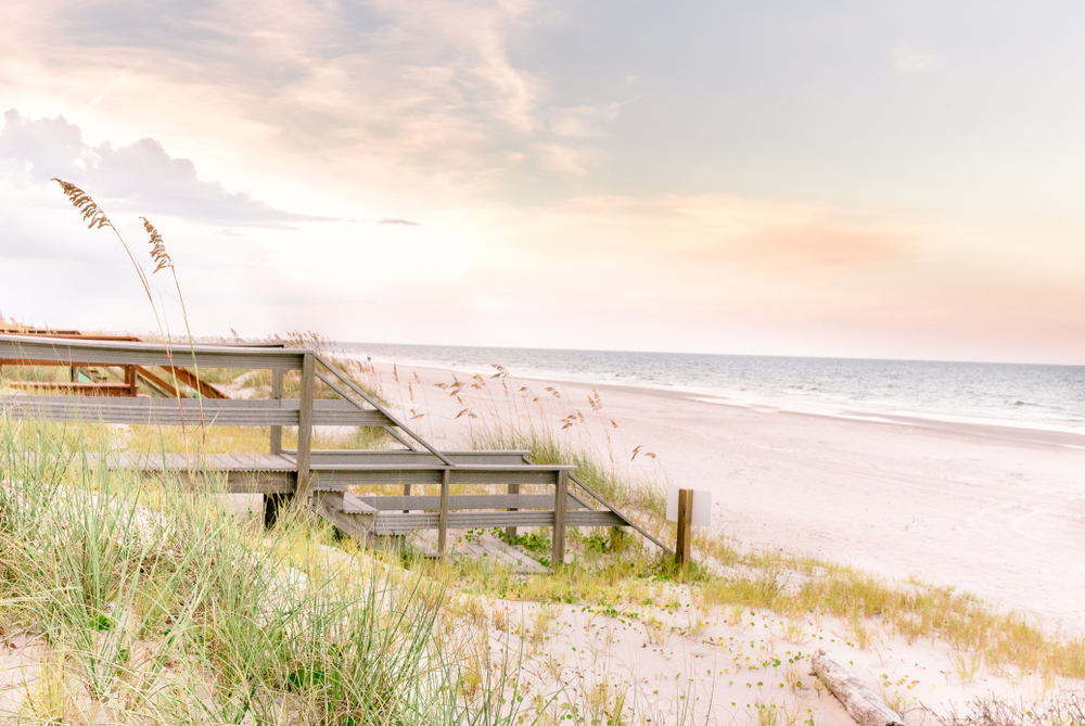 The sand dunes and a wooden walkway over them leading to the shore of the ocean at Amelia Island.