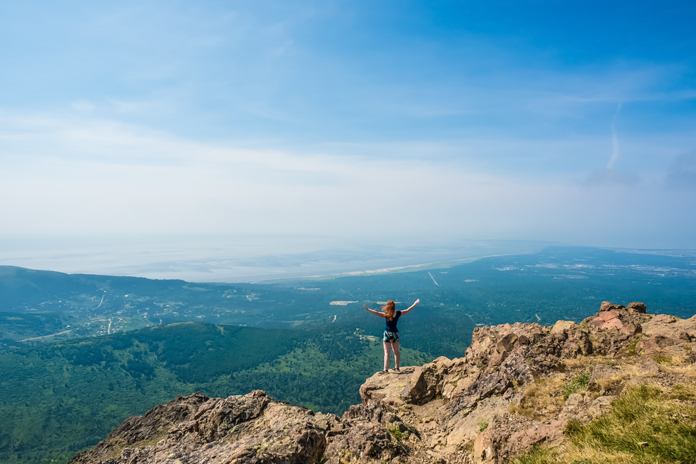 A woman with her hands spread wide on the edge of rocky cliff looking out to a valley. The valley is very green and has rolling hills and is in Anchorage Alaska. It is one of the best bachelorette party destinations.