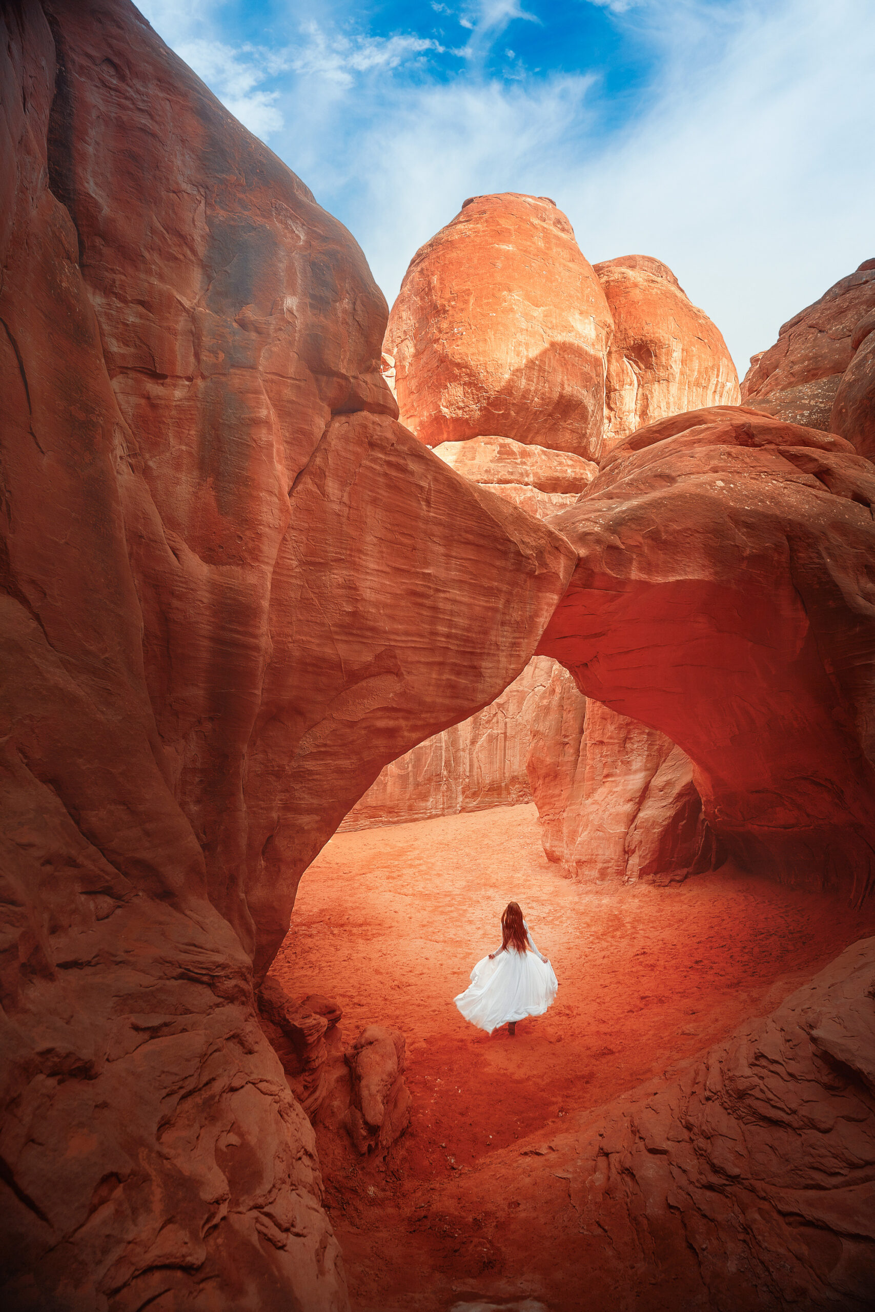A woman in a white dress with long hair running under a red sandstone arch. The area is nothing but red sandstone rock formations. Its a great Southwest road trip stop.
