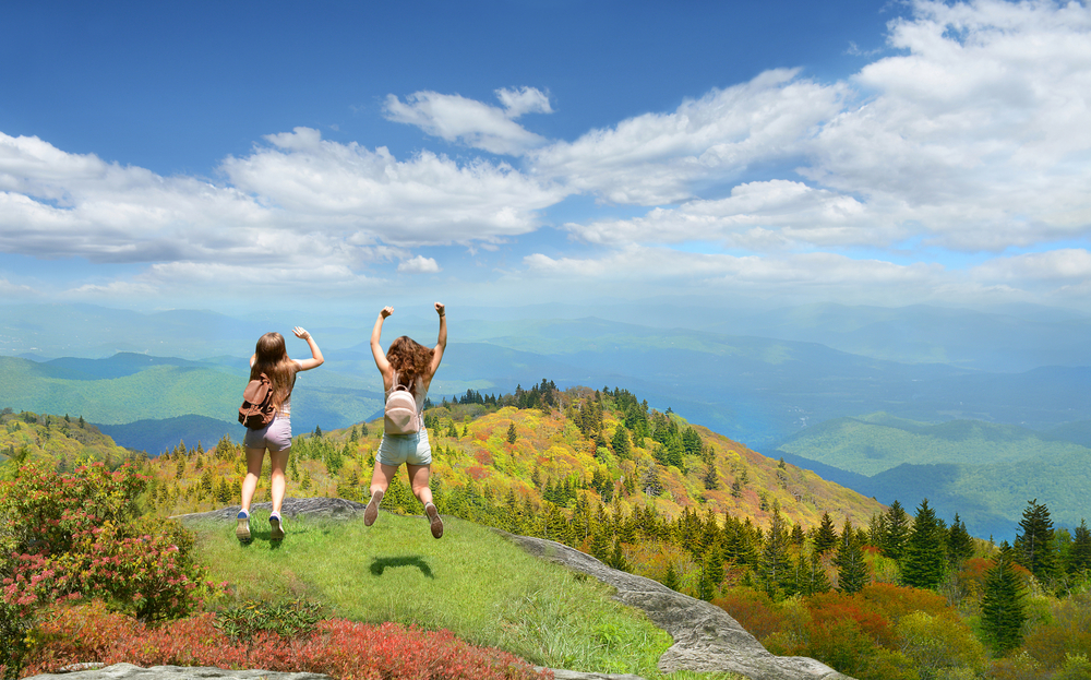 Two women jumping on the side of a mountain in Asheville North Carolina. They are facing the rolling mountains where you can see trees, valleys, and clouds shadowing the ground.