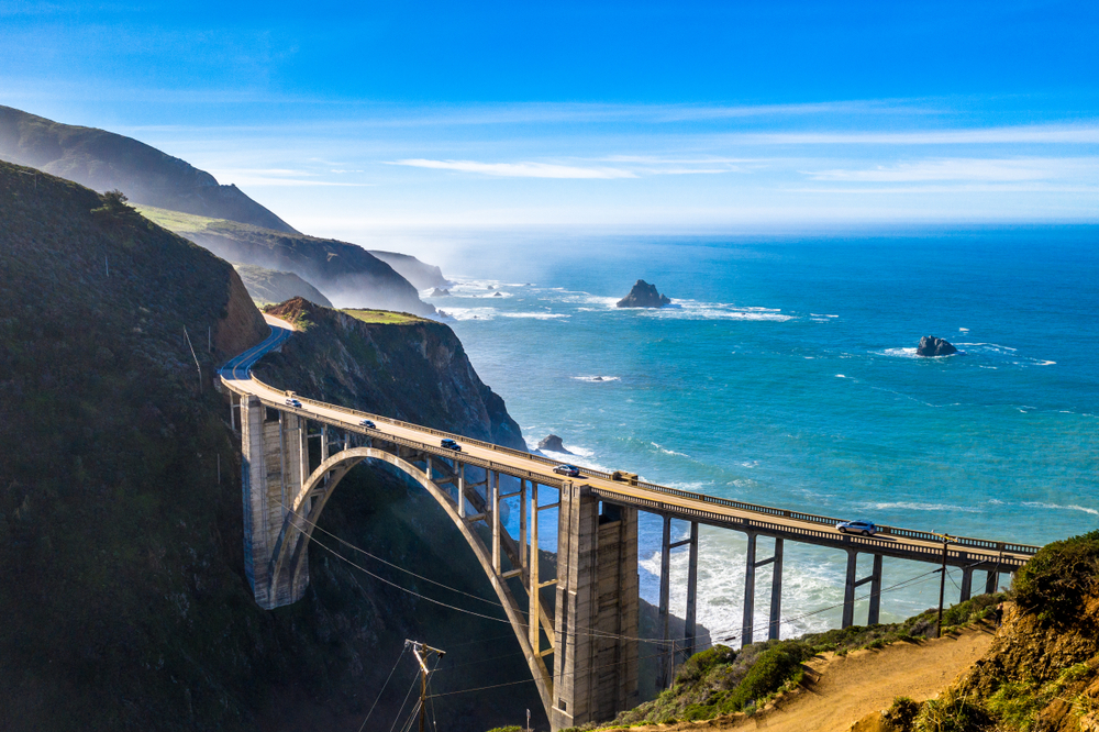 A side aerial view of the Bixby Bridge on a sunny day. You can see a few cars on the bridge and the pacific ocean with rock formations behind it. The mountains that the bridge leads to are in shadow. It is one of the most popular stops on any Big Sur road trip